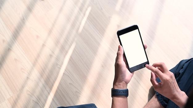 Capture d'écran d'un homme assis dans le salon et tenant un téléphone portable. écran vide pour le contenu d'un message texte ou d'informations.