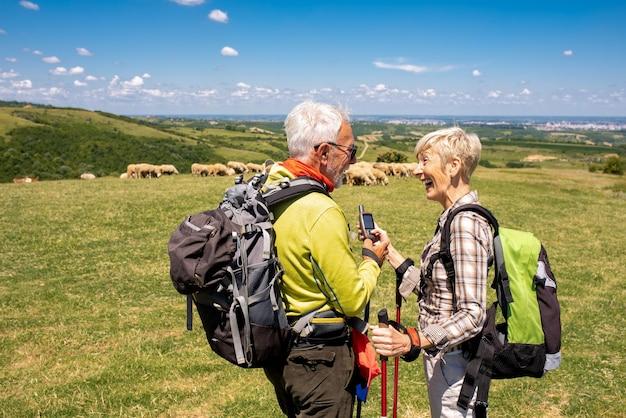 Capture d'écran peu profonde d'un couple âgé à l'aide d'une boussole électrique dans un grand champ