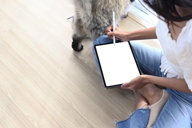 Capture d'écran d'une pigiste tenant un stylet écrivant sur l'écran de la tablette alors qu'elle était assise avec son chat sur le sol.