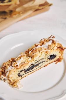 Capture en grand angle d'un délicieux morceau de gâteau aux graines de pavot avec un glaçage au sucre blanc sur une table blanche