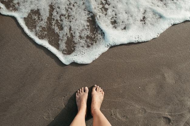 Capture en grand angle d'une personne debout sur la plage près de l'écume de mer
