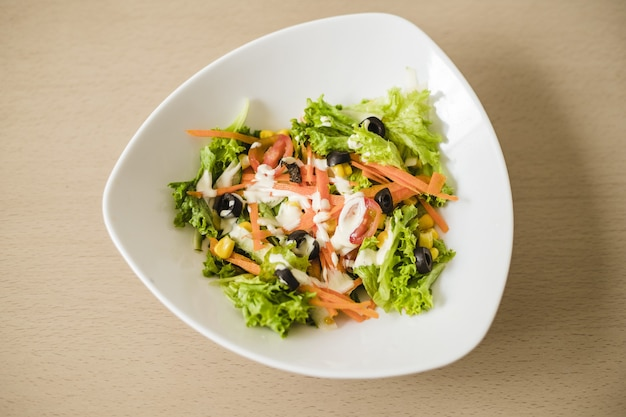 Capture en grand angle d'une salade de légumes dans un bol blanc