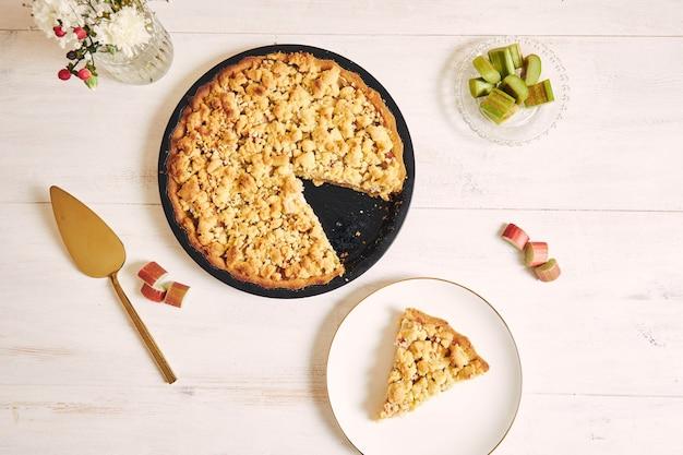 Capture en grand angle d'une tarte au gâteau rhabarbar croustillante et d'une tranche sur une assiette sur un tableau blanc