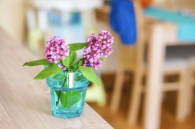 Capture sélective de brindilles de fleur de lilas dans un verre avec de l'eau sur une table en bois