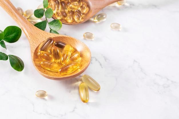 Capture sélective de capsules d'huile de poisson sur une cuillère en bois avec des feuilles vertes