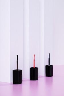 Capture verticale de brosses à vernis à ongles contre un mur blanc