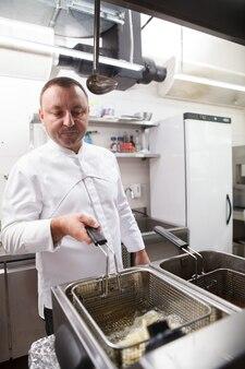 Capture verticale d'un chef masculin mature faisant frire des frites dans la cuisine de son restaurant
