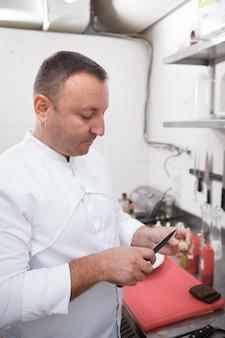 Capture verticale d'un chef professionnel ouvrant un œuf de caille avec un couteau