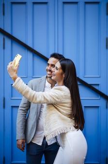 Capture verticale d'un couple d'amoureux caucasien faisant un selfie