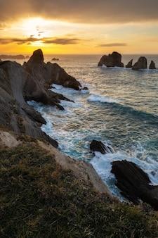 Capture verticale du coucher du soleil dans les urros de liencres, cantabrie, espagne