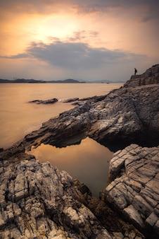 Capture verticale de l'eau et des falaises lors d'un coucher de soleil dans un ciel nuageux