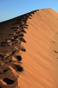 Capture verticale d'empreintes de pas sur les dunes de sable de xijiang, chine