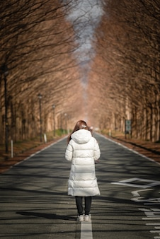 Capture verticale d'une femme debout sur une route vide