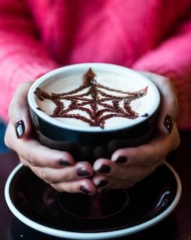 Capture verticale d'une femme avec une manucure sombre tenant une tasse de cappuccino avec une décoration en toile d'araignée