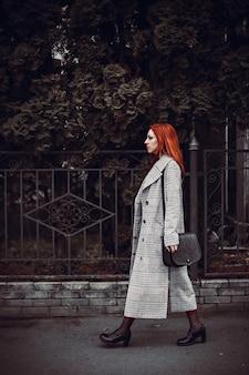 Capture verticale d'une femme multiraciale marchant près d'un parc de la ville