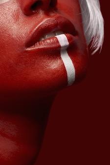 Capture verticale d'une femme en peinture corporelle rouge avec une ligne blanche sur fond rouge