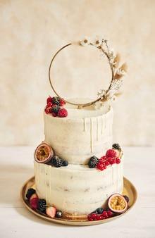 Capture verticale d'un gâteau de mariage décoré de fruits frais et de baies et d'un anneau de fleurs