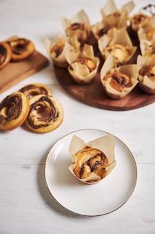 Capture verticale en grand angle de délicieux muffins et beignets au chocolat sur une table blanche