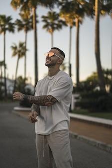 Capture verticale d'un homme élégant souriant aux bras tatoués