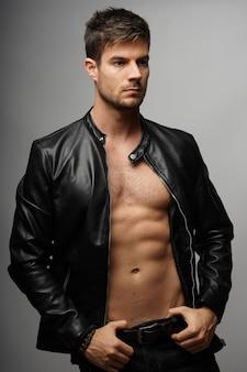 Capture verticale d'un homme portant un manteau de cuir sur un torse nu