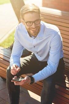 Capture Verticale D'un Jeune Homme D'affaires Gai Portant Une Chemise Bleue Et Des Lunettes à L'aide D'un Smartphone Photo Premium