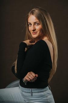 Capture verticale d'une jolie femme blonde posant assise sur un tabouret de bar