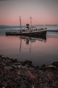 Capture verticale d'un navire en mer au coucher du soleil