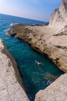 Capture verticale d'une personne nageant dans l'eau dans le parc naturel de cabo de gata-nijar en andalousie, espagne