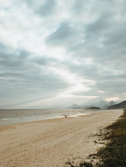 Capture verticale d'une plage entourée par la mer sous un ciel nuageux à rio de janeiro, brésil