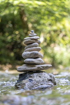Capture verticale d'une pyramide de pierres en équilibre sur l'eau d'une rivière