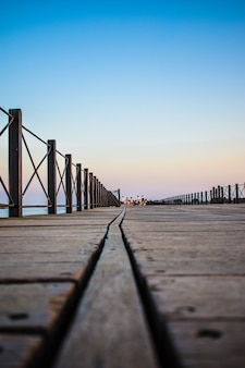 Capture verticale d'un quai en bois entouré de clôtures sous le ciel bleu le soir