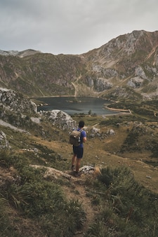 Capture verticale d'un randonneur masculin regardant un beau lac au parc naturel de somiedo en espagne