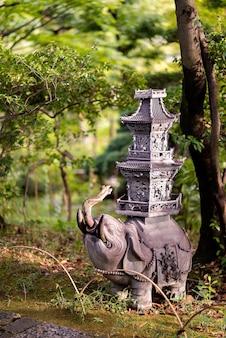 Capture verticale d'une statue d'éléphant dans un jardin de kyoto, japon