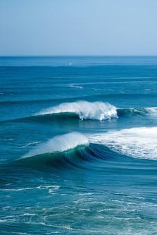 Capture verticale des vagues mousseuses de l'océan atlantique près de la municipalité de nazare au portugal