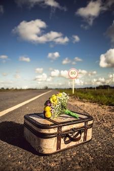 Capture verticale d'une valise vintage avec un bouquet sur une route vide