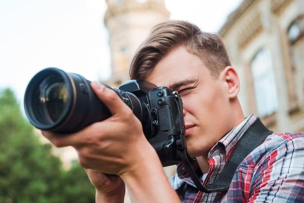 Capturer l'instant. beau jeune homme prenant une photo avec son appareil photo numérique en se tenant debout à l'extérieur
