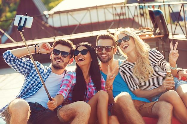 Capturer l'instant. vue de dessus de quatre jeunes joyeux qui se lient les uns aux autres et font un selfie sur un smartphone assis sur le toit