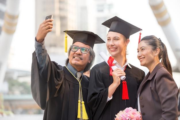 Capturer des moments heureux. heureux père et fille dans les robes de graduation faisant selfie.