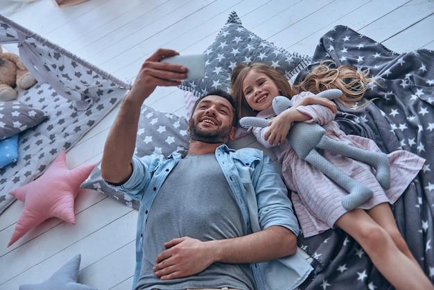 Capturer des moments lumineux ensemble. vue de dessus du père joyeux et de sa petite fille prenant un selfie allongé sur le sol à la maison ensemble