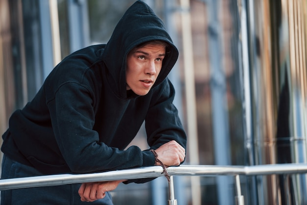 Avec capuche sur la tête. portrait de jeune principal en vêtements noirs qui s'appuie sur les balustrades et fait une pause.