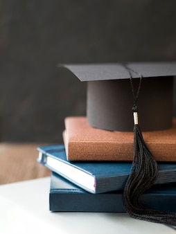 Capuchon de graduation vue de face sur une pile de livres