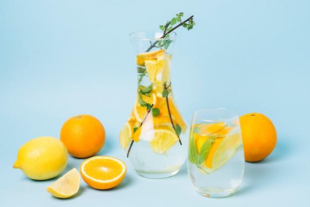 Carafe avec des oranges sur fond bleu