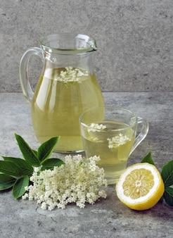Carafe et un verre avec une boisson de fleurs de sureau avec une tranche de citron.