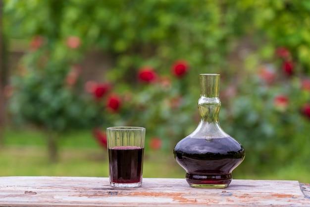 Carafe en verre et verre à vin rouge sur fond de jardin d'été sur table en bois, gros plan