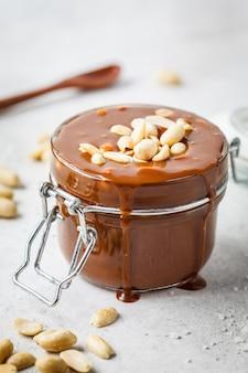Caramel salé fait maison avec noix dans un bocal en verre, espace de copie. ingrédient pour les gâteaux de gâteau.