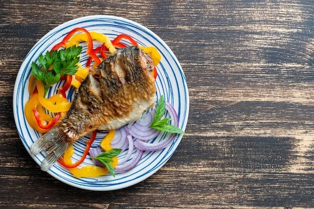 Carassin frit avec du poivre et de l'oignon sur une assiette sur un fond en bois. vue de dessus, gros plan