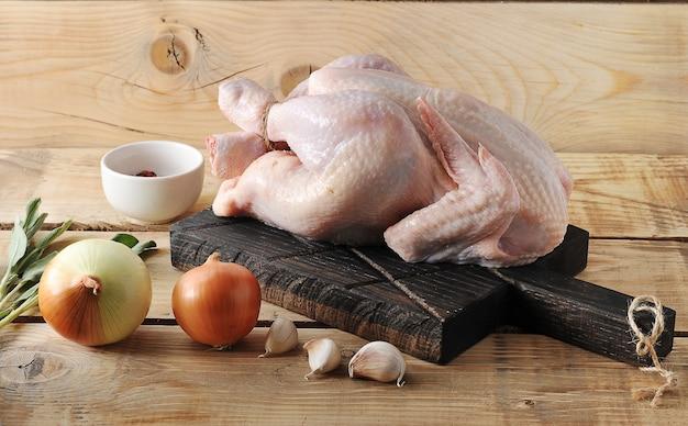 Carcasse entière de poulet cru au plateau et épices