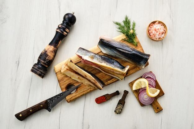 Carcasse de hareng congelé frais cru avec des épices sur une planche à découper