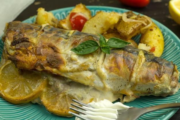 Carcasse de maquereau au four avec citron et légumes sur une assiette