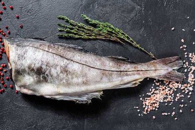 Carcasse de poisson d'aiglefin frais. fond noir.